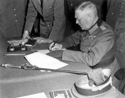 Маршал Кейтель подписывает акт «о безоговорочной капитуляции». На столе лежит его повседневный маршальский жезл.